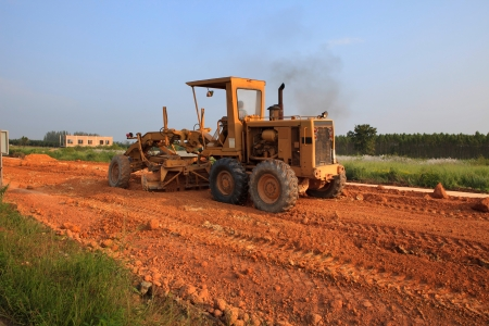 infra construction: heavy grader machine vehicle working on road construction site