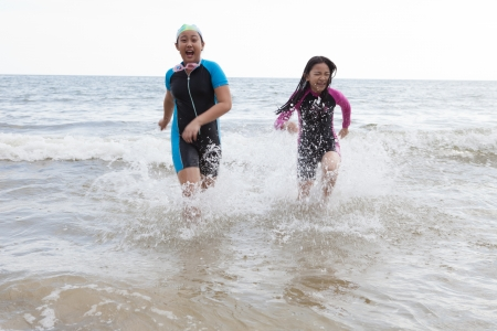 two girl wearing wet suit  playing on sea beach with happiness emotion  photo
