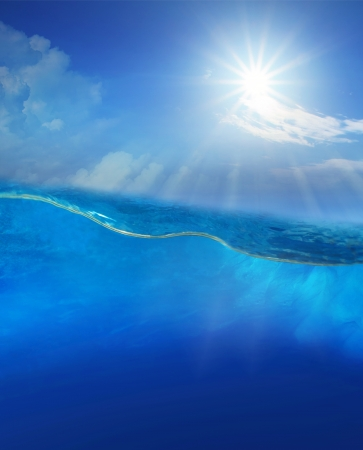 under blue water with sun shining above photo