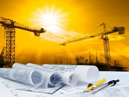 ingeniero civil: plan del arquitecto en la mesa de trabajo con la grúa y la construcción de edificios Foto de archivo