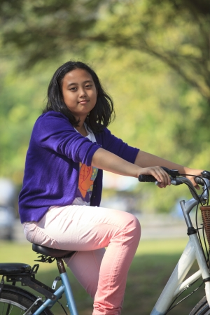 asian girl riding bicycle in public park with green blurry background use as for multipurpose in healthy life style topic photo
