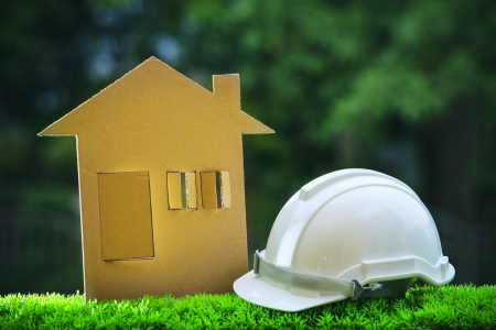 paper home out line with safety helmet on green grass field wtih blur copy space background use for real estate and land development topic photo