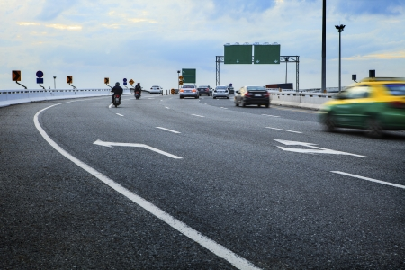 moving passenger car and motorcycle on bridge way crossing junction with blue sky background photo