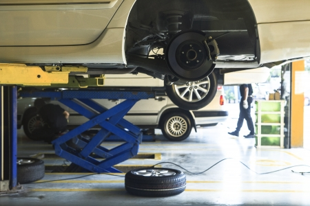 service lift:  car wheel  suspension and brake system maintenance in auto service before long journey