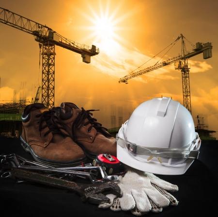 calzado de seguridad: casco y equipo de construcción con el edificio y la grúa contra el uso oscuro del cielo para la construcción de tema de negocios