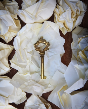 find out: file golden key on crumpled paper on wood table seem some successfull was not find out  Stock Photo