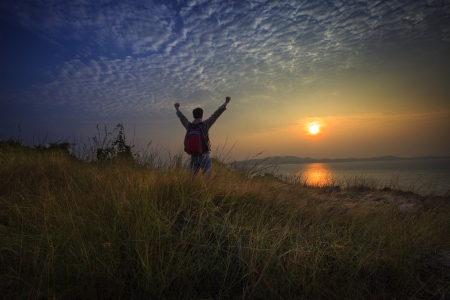 young man standing and rising hand as victory on grass hill looking to sun above sea horizontal with dramatic colorful sky background photo