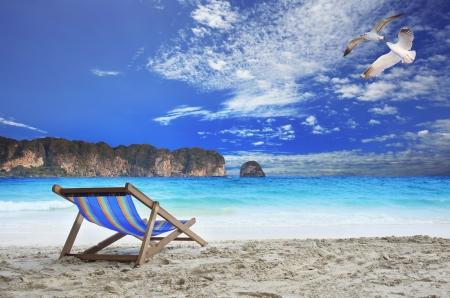 madera sillas de playa al borde del mar con las aves gaviota hermosa del vuelo en el cielo azul y piedra isla l�nea contra el uso horizontal oc�ano como las vacaciones y las vacaciones de fondo natural photo