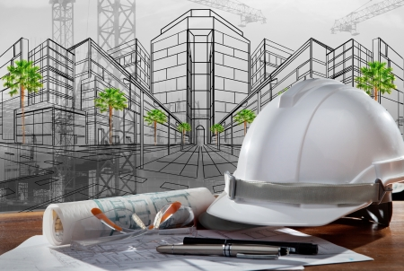 safety helmet and architect plan on wood table with sunset scene and building construction photo