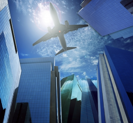 passenger plane flying over modern office building against blue sky white cloud seem city life and air transport business scene photo