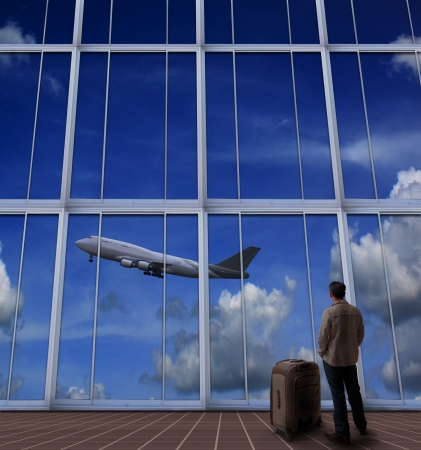 runways: passenger standing with big suitcase in airport and looking to air plane take off from runway  Stock Photo