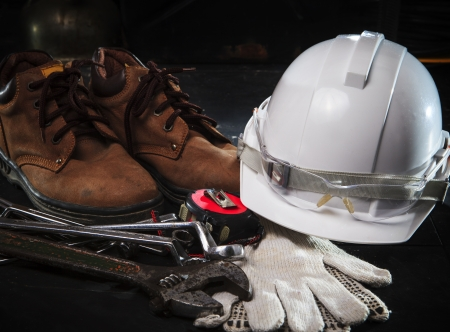 safety shoe and safety helmet with construction equipment with low key light use for construction industry topic photo