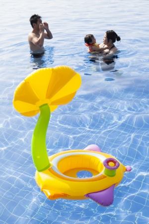 family in water pool with children toy playing with happiness photo