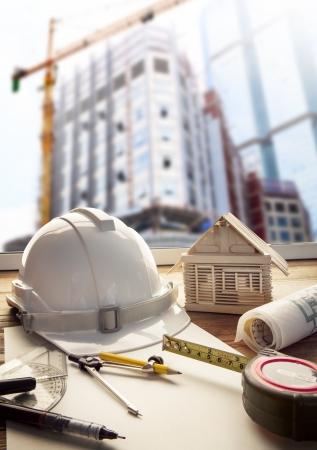 palazzo: casco di sicurezza piano di stampa blu e macchine per le costruzioni su architetto e ingegnere tavolo di lavoro con la costruzione di edifici Archivio Fotografico