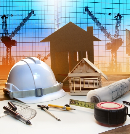 ingeniero civil: torre de oficinas y el hogar plan de construcci�n en la mesa de trabajo del arquitecto con el edificio moderno y el uso del fondo de la gr�a para el ingeniero civil y de escena contexto arquitect�nico