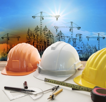 Casco de seguridad sobre el arquitecto, mesa de trabajo ingeniero con moderno edificio y la construcción de grúas Foto de archivo - 25207791