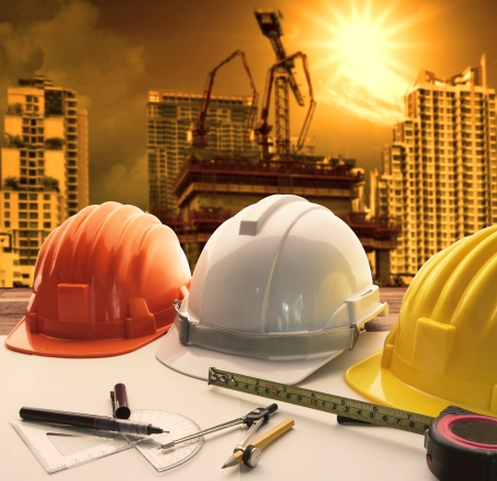 safety helmet on architect ,engineer working table with modern building and crane construction background use for construction business and civil engineering ,real estate topic photo