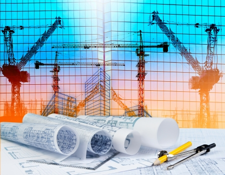 architecture plan on architect working table with building and reflection of crane construction on mirror building photo