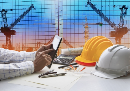 engineering plans: hand of architect working on table with tablet computer and working tool equipment against reflection of office building and crane construction use for civil engineering and construction industry business