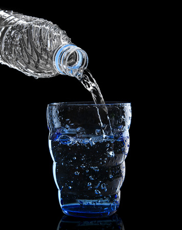 freshness cool and clean drinking water pouring to blue glass isolated on black background use for healthy care food and drink beverage  photo