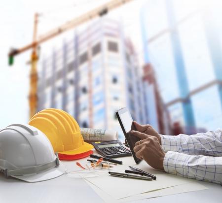 건축가는 태블릿 컴퓨터와 함께 테이블에 작업 및 토목 공학 및 건설 업계의 비즈니스를위한 사무실 건물 및 크레인 건설의 반사에 도구 장비를 작업