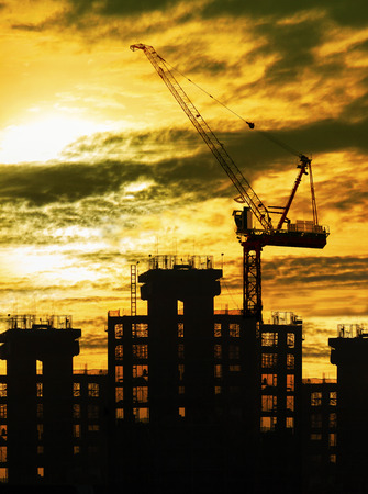 land management: silhouette of crane and building construction and sun set sky with copy space use for construction industry business theme Stock Photo