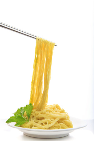 steel chopstick holding chinese yellow eggs noodle on white disk with green leaves of  celery ready to eating meal on white background  Stock Photo
