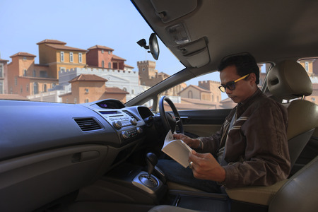 asian man stop a car and looking to a book against building out side  photo