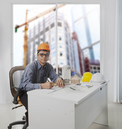 land management: architect engineer working in office room against building construction through mirror window  use for architecture and engineering construction industry business theme and real estate land management Stock Photo