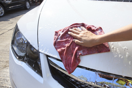 hand with soft clothes washing passenger car at home photo