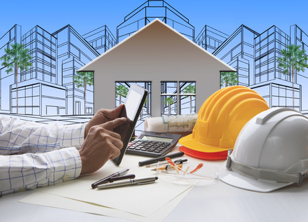 de hand van de architect werken op de computer tablet met bouw en ingenieur werkinstrument bovenop tafel tegen huis uit lijn en schetsen van het moderne gebouw perspectief