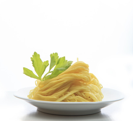 asian noodle: chinese yellow eggs noodle on white disk with green leaves of celery ready to eating meal on white background Stock Photo