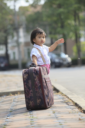 young children standing with big suitcase beside traffic street and waiting car to going on Stock Photo - 26138405