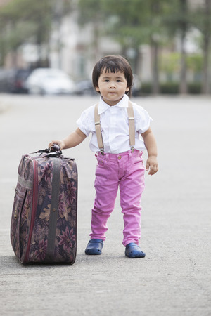 asian children walking on street with big suitcase use for journey and traveling of kid and adorable young kid topic  photo