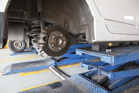 brake caliper: maintenance of sedan car suspension shock absorber and brake caliper in auto car service Stock Photo