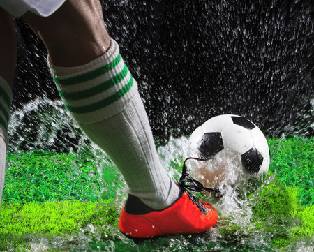football socks: soccer football players kicking to soccer ball on green grass field with splashing of transparent water against black background Stock Photo