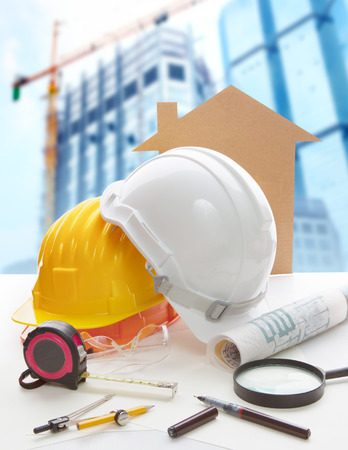 building structures: safety helmet blue print plan and construction equipment on architect ,engineer working table with building construction crane background use for construction industry business and civil engineering  Stock Photo