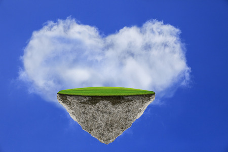 heart under: floating green grass field island with white cloud heart shape against blue sky background