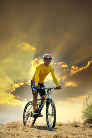 young man riding moutain bike mtb on land dune against dusky sky in evening background  use for sport leisure and out door activities theme Stock Photo