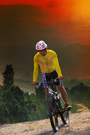 out door: young man riding mountain bike bicycle crossing mountain hill jungle track with dusky sky scene use for out door sport and exteme activities lifestyle