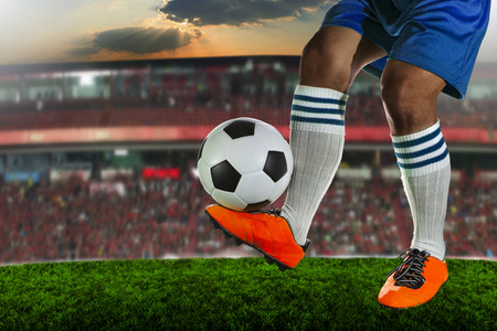 soccer shoes: foot ball player holding foot ball on leg ankle on soccer sport field agianst stadium and dusky sky use for soccer footbal teaml competition