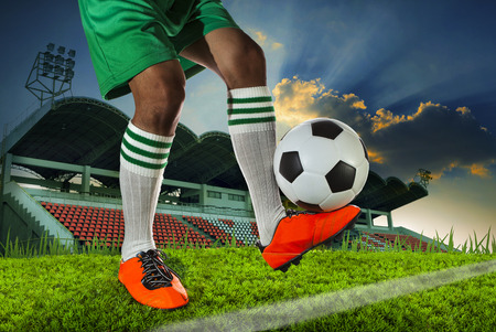 football socks: foot ball player holding foot ball on leg ankle on soccer sport field agianst stadium and dusky sky use for soccer footbal teaml competition