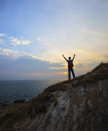 young man standing on rock cliff and rising victory hand against dusky sky  photo