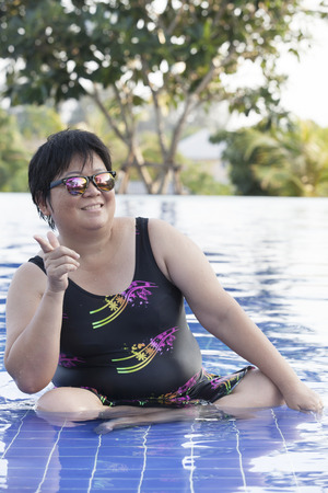 self confidence: chubby woman wearing swimming suit and  wearing sun glasses with self confidence acting relaxing emotion