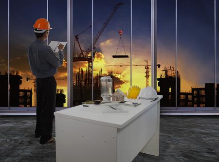 ingeniero civil: ingeniero masculino comprobando el flujo de trabajo en la obra de construcción contra el uso hermoso cielo oscuro para las empresas de construcción e ingeniería civil Foto de archivo