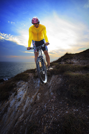 young man riding moutain bike mtb on land dune against dusky sky in evening background use for sport leisure and out door activities theme photo