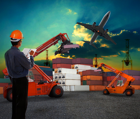working man in logistic business working in container shipping yard with dusky sky and jet plane cargo flying above use for land to air transport and freight photo