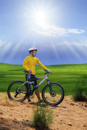 out door: young man standing beside moutain bike ,mtb on hill with sun shining on blue sky use for sport leisure and out door activities extreme sport theme
