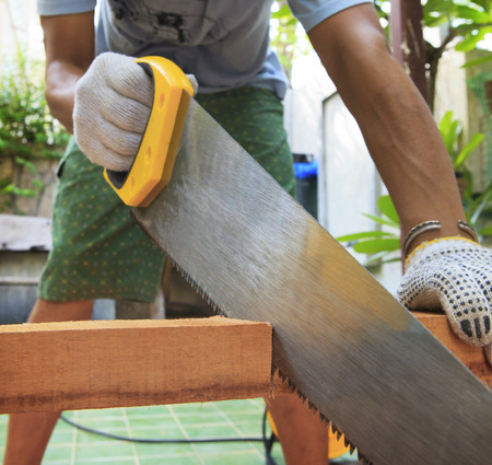 home maintenance: young man sawing wood at home use for diy working and home maintenance in holiday and male activities