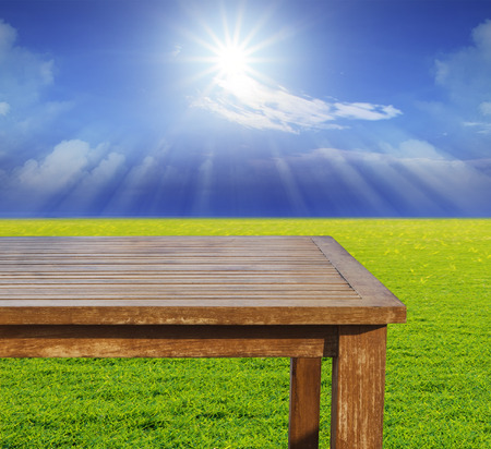 out door: empty free space top wood table on green grass field against sun beam on blue sky use for multipurpose background ,backdrop